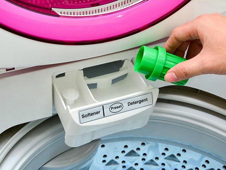 Đổ nước xả vào khay đựng trên máy, tránh đổ trực tiếp